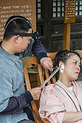 Local Chinese medicine, ear cleaning in a park photographed in Chengdu, Kuan Zhai Xiang Zi historic city. Sichuan, China