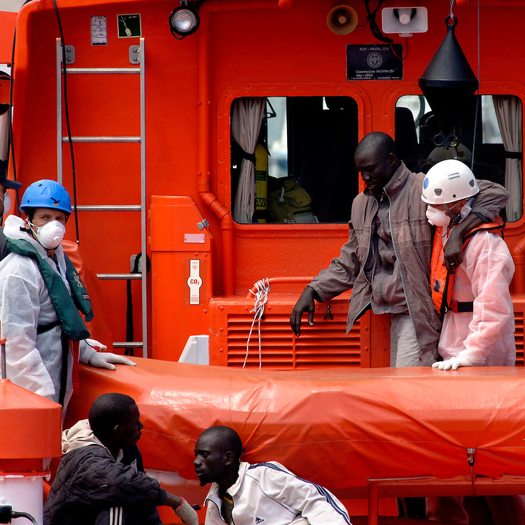 """Tenerife / Los Cristianos June 7, 2006 - would-be immigrants is helped to get off a boat at his arrival  at the canary islands  -  A fishing boat called """"Cayucos"""" by the inhabitants of the island, with 85 would-be immigrants from West Africa intercepted by Spanish police of the coast of Tenerife in the Canary Islands are seen in an open wooden fishing vessel as they approach the port of Los Cristianos. They arrived on June, carrying 85 would-be immigrants, in the archipelago which has received more than 7,000 Africans so far this year, more than half to the tourist resort island of Tenerife. At least 1,000 more are believed to have died trying to make the sea crossing, mostly in small fishing boats"""