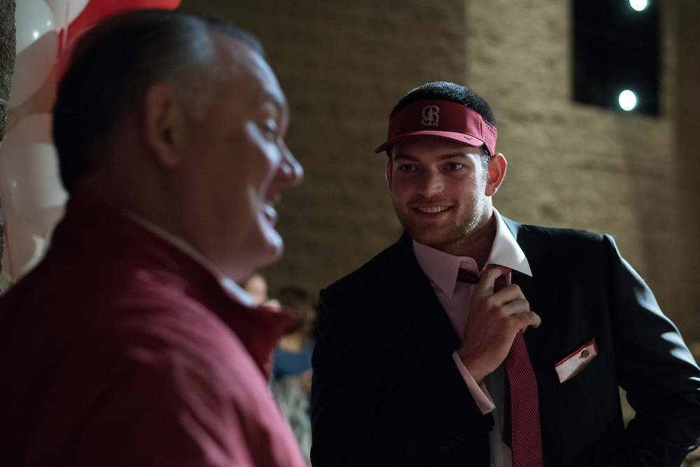 Flower Mound Marcus High School senior tight end Kaden Smith loosens his tie while chatting with his father, Marc, after signing his National Letter of Intent to play football at Stanford University during his high school signing day on February 3, 2016. (Cooper Neill for The New York Times)