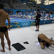 Swimmers stretching before swimming at the Aquatic Centre at Olympic Park, Stratford during the London 2012 Olympic games preparation at the London Olympics. London, UK. 25th July 2012. Photo Tim Clayton