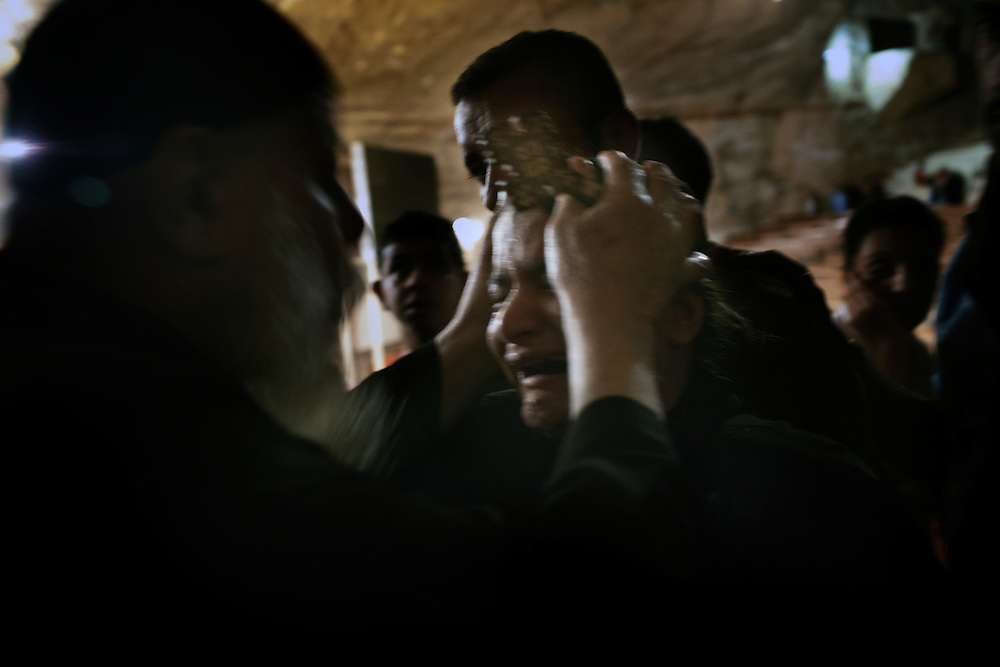 A Coptic priest perfom exorcism on a  worshipper in the Cave Cathedral or St. Sama'ans Church in garbage city,Cairo. <br /><br />Garbage city, Mansheet Nasser, is a slum in Cairo inhabited by a community of about 50.000 Christians Copts mainly working in the activity of recycling the garbage. The Zabelleen, garbage pickers, collect the garbage of the whole city of Cairo and bring it to Garbage city where it were differentiated to be sold as raw material or recycled in the slum. Despite the unhealthy condition of life and work, the workers involved in this activity can earn until 60 egyptian pound a day (6 euro), more than public servants  minimum wage.