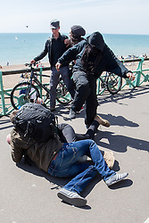 © Licensed to London News Pictures . 21/04/2013 . Brighton , UK . Those for and against the march fight on the seafront . Two men scuffle as a third kicks one . Nationalist group March for England hold a march along Brighton seafront today (Sunday 21st April) . The group was supported by supporters of the English Defence League and opposed by anti fascist and left wing groups . The annual march takes place close to St George's Day and frequently results in scuffles and violence between opposing groups and police . Photo credit : Joel Goodman/LNP