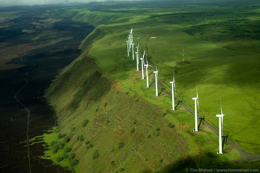 A token array of wind turbines stands on the edge of a lava flow on Hawaii Island, a place where the bulk of the electricity is from massive diesel generators.