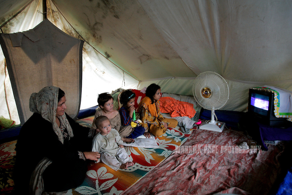 MUZAFFARABAD, PAKISTAN - SEPTEMBER 21: A family watches television in a tent village in earthquake-stricken Kashmir, September 21, 2006, Muzaffarabad, Pakistan. One year after an earthquake struck the region, hundreds of thousands of people face many obstacles in rebuilding their shattered communities.The South Asia earthquake measured 7.6 on the Richter Scale in Pakistan Administered Kashmir just before 9am on Saturday, October 8, 2005 and is the twelfth most destructive earthquake in recorded history, killing 87,000 and internally displacing 3 million. Early assessments indicate it will take upwards of 10 years for the affected regions to fully recover from the damage, however, scientists estimate the region should prepare for future earthquakes on a much larger scale, citing the Eurasian and Indian tectonic plates running through Kashmir as extremely unstable. (Photo by Warrick Page)