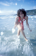A girl, in a red bikini, smilling having fun, splashing around in the sea, UK 2004