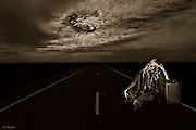 portrait of traveller waiting beside an empty highway with dramatic stormy clouds