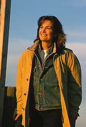woman outdoors during a sunset smiling and looking off
