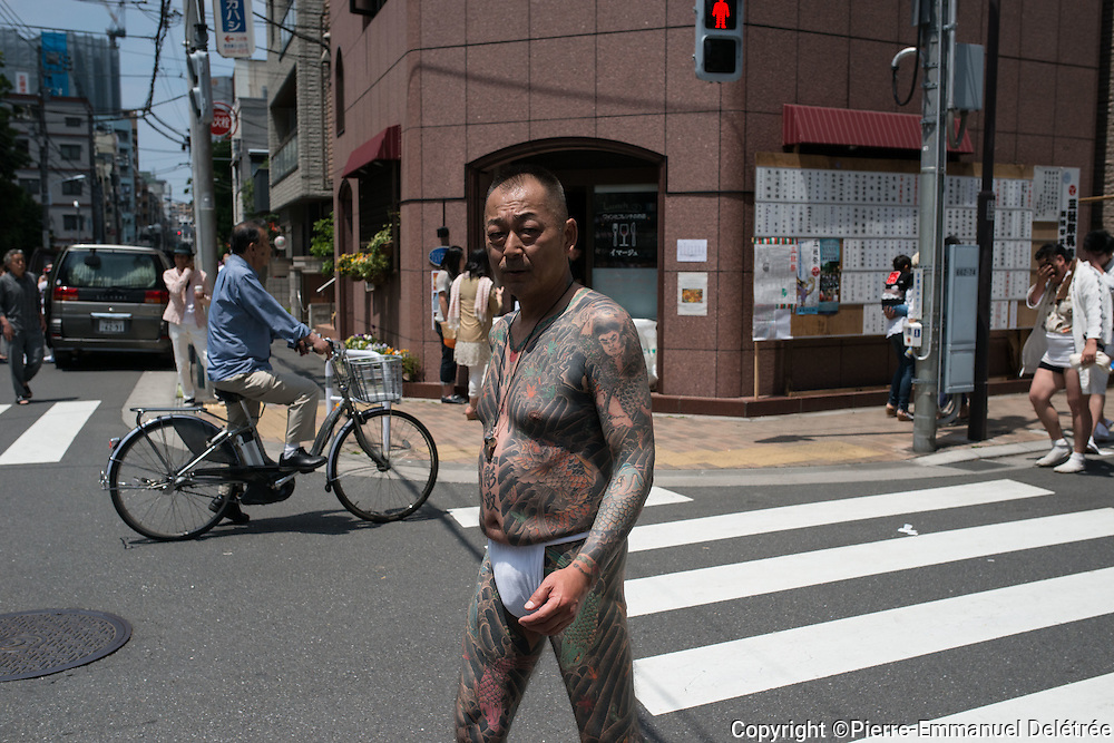 TOKYO, JAPAN - MAY 14: Yakuza member proudly display his tattoos during the second day of the Sanja Matsuri Festival in Tokyo's Asakusa district on May 14, 2016. This festival is one of the rare times when members of the notorious Yakuza gang reveal themselves to public and take photo with festival goers.
