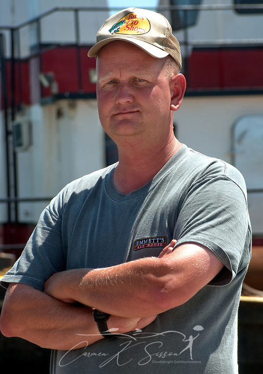 Magnolia Springs Volunteer Fire Department Chief Jamie Hinton stands in front of a spud barge June 11, 2010 in Magnolia Springs, Ala. Hinton is leading the town in a fight to protect the area from encroaching oil by blocking the entrance to Weeks Bay with barges and layers of containment boom following the explosion of the Deepwater Horizon oil rig and BP oil spill. (Photo by Carmen K. Sisson/Cloudybright)