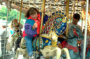 Down syndrome woman age 32 giving thumbs up on carousel.  St Paul  Minnesota USA