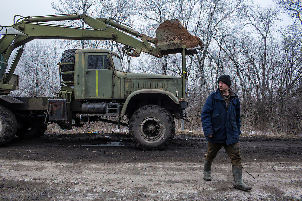 ARTEMIVSK, UKRAINE - FEBRUARY 14: A Ukrainian soldier with a military truck on the road between Artemivsk and the embattled town of Debaltseve on February 14, 2015 in Artemivsk, Ukraine. A ceasefire between Ukrainian forces and pro-Russian rebels is scheduled to go into effect at midnight. (Photo by Brendan Hoffman/Getty Images) *** Local Caption ***