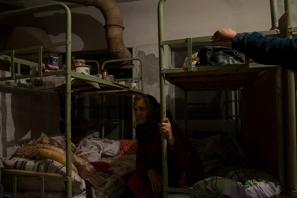 An elderly woman takes shelter in the basement of a former factory in Donetsk.