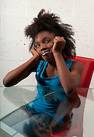 African American girl seated and smiling with pensive look.