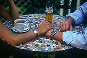A couple hold hands while enjoying a tea and a beer at an outdoor cafe, on 11th June 1999, in Seville, Andalucia, Spain.