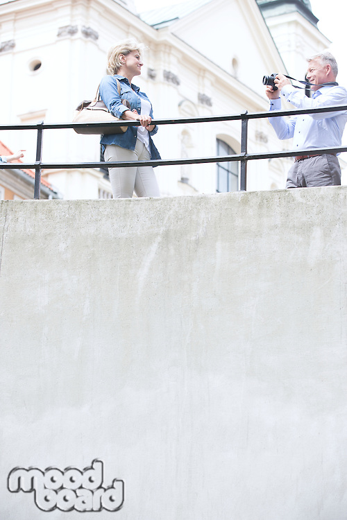 Low angle view of man photographing woman by railing outside church