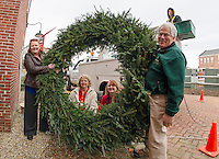 Denise Sharlow and Peter Ellis from the Belknap Mill with Marge Dyer and Donna Vernon from Opechee Garden Club (in center of wreath) and Matt Giuffrida from Hutchins Electric as they prepare to hoist the wreath donated by the Opechee Garden Club to hang on the Belknap Mill.   (Karen Bobotas/for the Laconia Daily Sun)