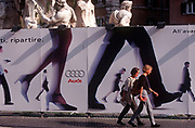 Two women walk past a billboard for car maker Audi in Piazza Navona, on 3rd November 1999, in Rome Italy. (Photo by Richard Baker / In Pictures via Getty Images)
