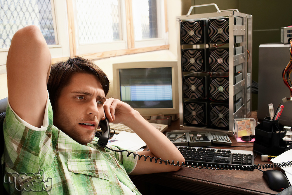 Man using phone with computer equipment in background.