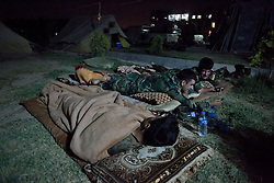 © Licensed to London News Pictures. 29/06/2014. Khanaqin, UKKhanaqin, Iraq. Two Kurdish peshmerga fighters look at a video clip on a mobile phone as another sleeps at a Kurdish peshmerga base in Khanaqin, Iraq.<br />  ween snipers and heavy machine guns on both sides.<br /> <br /> The peshmerga, roughly translated as those who fight, is at present engaged in fighting ISIS all along the borders of the relatively safe semi-automatous province of Iraqi-Kurdistan. Though a well organised and experienced fighting force they are currently facing ISIS insurgents armed with superior armament taken from the Iraqi Army after they retreated on several fronts. Photo credit : Matt Cetti-Roberts/LNP