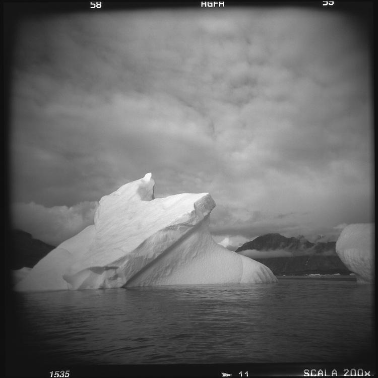 Greenland, Nanortalik, Blurred black and white Holga image of melting iceberg near mouth of Tasermiut (Ketils Fjord) on summer evening
