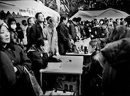 Experts advise homeless man (seated center right) at tent village set up by a Japanese NPO (non-profit organization) in Tokyo's Hibiya Park while others listen to protest speakers, Tokyo, Japan.