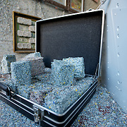 March 27, 2012 - Dublin, Ireland: A suitcase full of shredded money on display at the Billion Euro House art installation by the Irish artist Frank Buckley. ..Worthless euros, taken out of circulation and shredded by Irelands Central Bank, formes the interior walls of an apartment that Mr. Buckley does not own in a building left vacant by the countrys economic ruin...The artist decided to call the apartment  built from thousands of bricks of shredded, decommissioned cash (each brick contains, roughly, what used to be 50,000 euros)  the Billion Euro House. He reckons that about 1.4 billion euros actually went into it, but the joke, of course, is that it is worth simultaneously so much and so little...A large gravestone beside the main door, announces that Irish sovereignty died in 2010, the year that the government accepted an international bailout so larded with onerous conditions that the Irish will be paying for it for years to come. (Paulo Nunes dos Santos/Polaris)