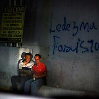 VENEZUELAN POLITICS / POLITICA EN VENEZUELA<br /> Two men sat talking in a gas station overnight / Dos hombre sentados conversando en una stacion de gasolina durante la noche<br /> Caracas - Venezuela 2009<br /> (Copyright © Aaron Sosa)