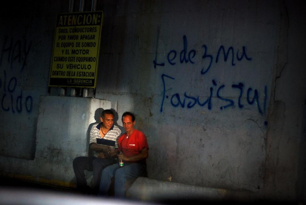 VENEZUELAN POLITICS / POLITICA EN VENEZUELA<br /> Two men sat talking in a gas station overnight / Dos hombre sentados conversando en una stacion de gasolina durante la noche<br /> Caracas - Venezuela 2009<br /> (Copyright &copy; Aaron Sosa)