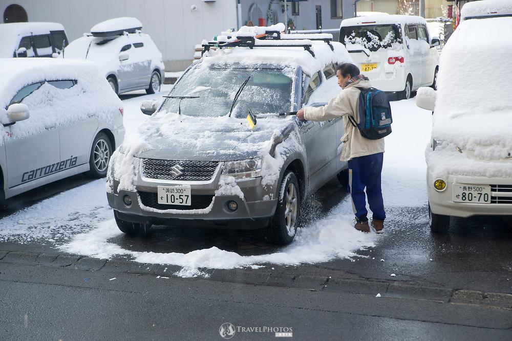 A man clearing snow off of his car at Yudanaka, Nagano.