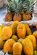 Papayas and pineapples at a fresh fruit stand at the Sunday market in Tlacolula de Matamoros, Mexico. The regional street market draws thousands of sellers and shoppers from throughout the Valles Centrales de Oaxaca.