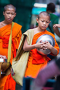 09 OCTOBER 2012 - BANGKOK, THAILAND:  Novice Buddhist monks walk through the Bangkok Flower Market. Most males in Thailand enter the Sangha (become Buddhist monks) at least once in their lives. Their time in the Sangha may be as short as a few weeks or as long as a lifetime commitment. The Bangkok Flower Market (Pak Klong Talad) is the biggest wholesale and retail fresh flower market in Bangkok. It is also one of the largest fresh fruit and produce markets in the city. The market is located in the old part of the city, south of Wat Po (Temple of the Reclining Buddha) and the Grand Palace.    PHOTO BY JACK KURTZ