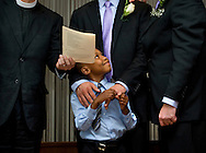 (L-R)  Newly-adopted son Cardel, 6 smiles at his two adoptive parents,  Kelly Vielmo (C) and Jack Montgomery (R) get married by Rev. John Beddingfield in Washington, DC on Thursday, July 26, 2012.  The same sex couple legally adopted Cardel and his two sisters Ravyn, 2 and Raine, 3 earlier in the day.  The children are all siblings from the same mother and have been living with Jack and Kelly for about a year now.  They decided to do both events on the same day out of convenience for family members who came to town.<br /> (photo by Linda Davidson/The Washington Post)