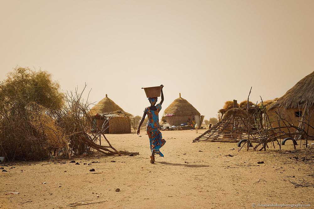 Dank eines von HEKS mitfinanzierten Bohrbrunnen können Frauen im sehr heissen und trockenen YOUNOUFERE in Senegal einen Garten anlegen und  Gemüse anbauen.  Das Bild zeigt Frauen auf dem Heimweg vom Garten in ihr Dorf.