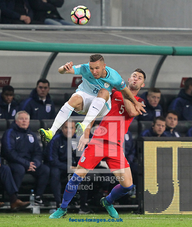 Jasmin Kurtić of Slovenia and Gary Cahill of England in action during the 2018 FIFA World Cup Qualifying match at SRC Stozice, Ljubljana<br /> Picture by Paul Chesterton/Focus Images Ltd +44 7904 640267<br /> 11/10/2016