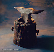 An old anvil photographed in the studio on a painted background.