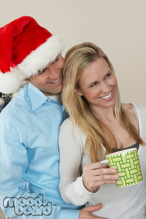 Man in Santa hat with arm around woman with coffee cup