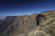 Hikers stand at the top of Tugela River falls at the top of the Amphitheatre. in the Drakensberg mountains of South Africa. Known as uKhahlamba in Zulu which means barrier of the spears. The mountains form a barrier between South Africa and Lesotho and are a world heritage site. The largest proportion of the Drakensberg area falls in the province of KwaZulu-Natal.