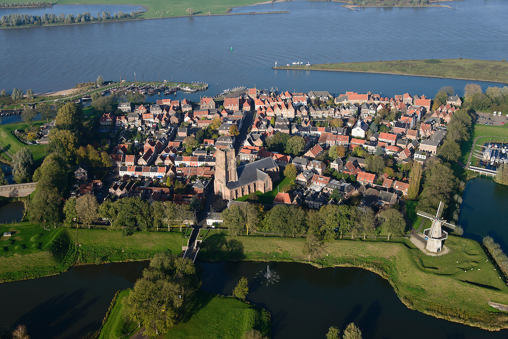 Nederland, Noord-Brabant, Woudrichem, 28-10-2014; vestingstad in Land van Heusden en Altena. Gelegen op de plaats waar de Maas (nu Afgedamde Maas) in de Waal stroomt en verder gaat als Boven-Merwede. In het centrum de Martinuskerk, buiten de stadsmuren molen Nooit Gedagt (korenmolen).<br /> Fortified town in Land of Altena. Located at the place where the Maas (Meuse) flows in the river Waal river, continuing under the name of Boven-Merwede. In the center church of Saint Martin, outside the city walls the mill Never thought fit (flour mill)<br /> luchtfoto (toeslag op standard tarieven); aerial photo (additional fee required); copyright foto/photo Siebe Swart
