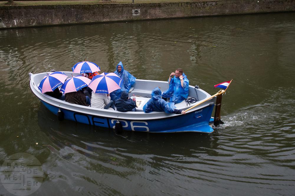 Een groep toeristen vaart in een boot door Utrecht.<br /> <br /> A group tourists is sailing in a boat at the canals of Utrecht.