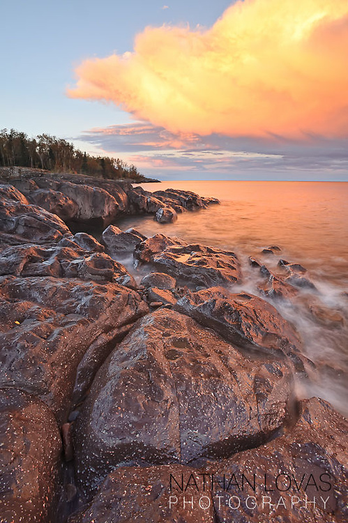 Lake Superior sunsetwith orange clouds and rocky shoreline;  Temperance River, Minnesota.
