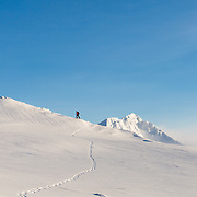 Arnar Felix Einarsson walking on skis on mt. Haki with mt. Hornklofi in the background, Tindfjöll mountain range, Iceland.