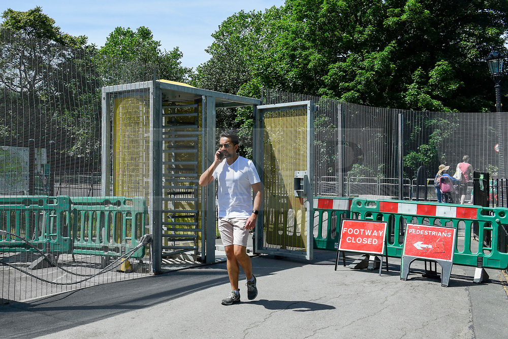 © Licensed to London News Pictures. 01/06/2019. LONDON, UK.  A member of the public passes through a security gate in fences which have been installed around Winfield House in Regent's Park ahead of the State Visit of President Donald Trump.  Winfield House is the residence of the Ambassador of the United States of America to the Court of St. James's and will host the US President during his visit.  Photo credit: Stephen Chung/LNP
