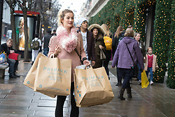 © Licensed to London News Pictures. 22/12/2017. London, UK. A woman with several shopping bags in Oxford Street in London on the last Friday before Christmas. Photo credit: Vickie Flores/LNP