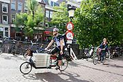 In Utrecht geeft een fietskoerier richting aan als hij met een bakfiets over de Oudegracht fietst.<br /> <br /> In Utrecht a bike courier is cycling on a cargo bike.