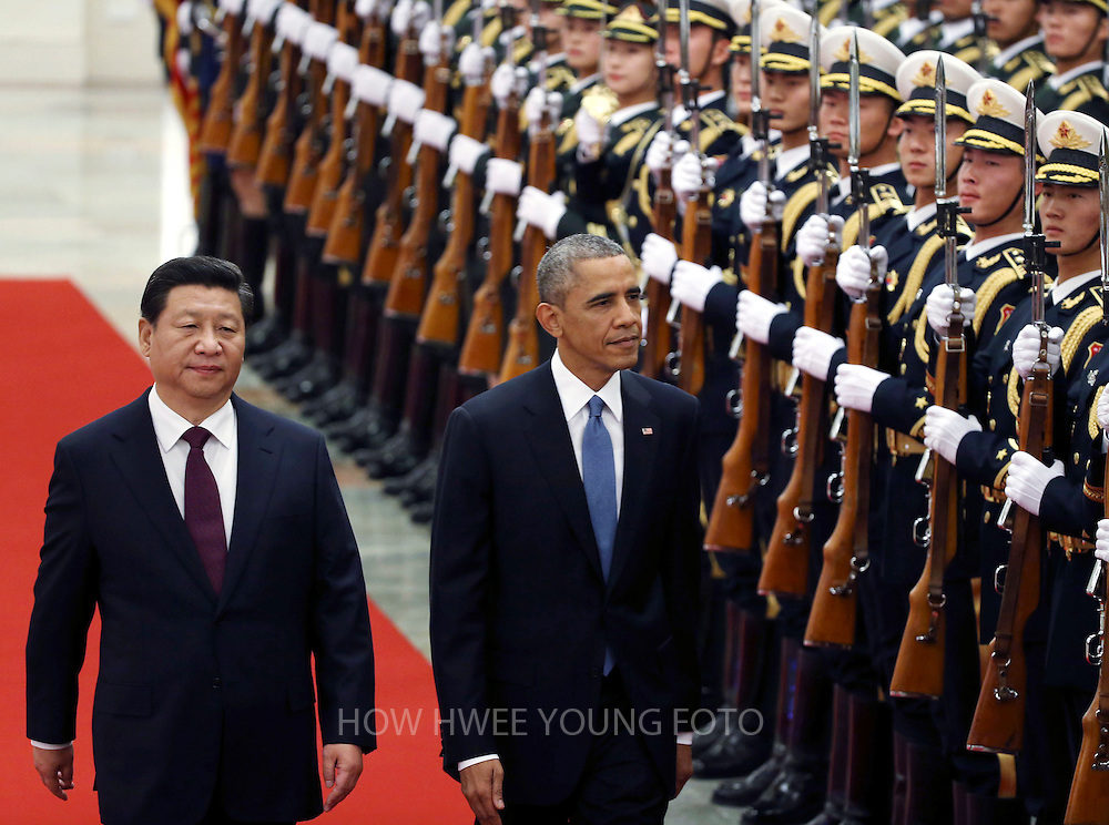 epa04485892 US President Barack Obama (2-L) and Chinese President Xi Jinping (L) review honor guards during a welcome ceremony at the Great Hall of the People (GHOP) in Beijing, China, 12 November 2014. Obama is in China to attend the Asia-Pacific Economic Cooperation (APEC) 2014 Summit and related meetings.  EPA/HOW HWEE YOUNG