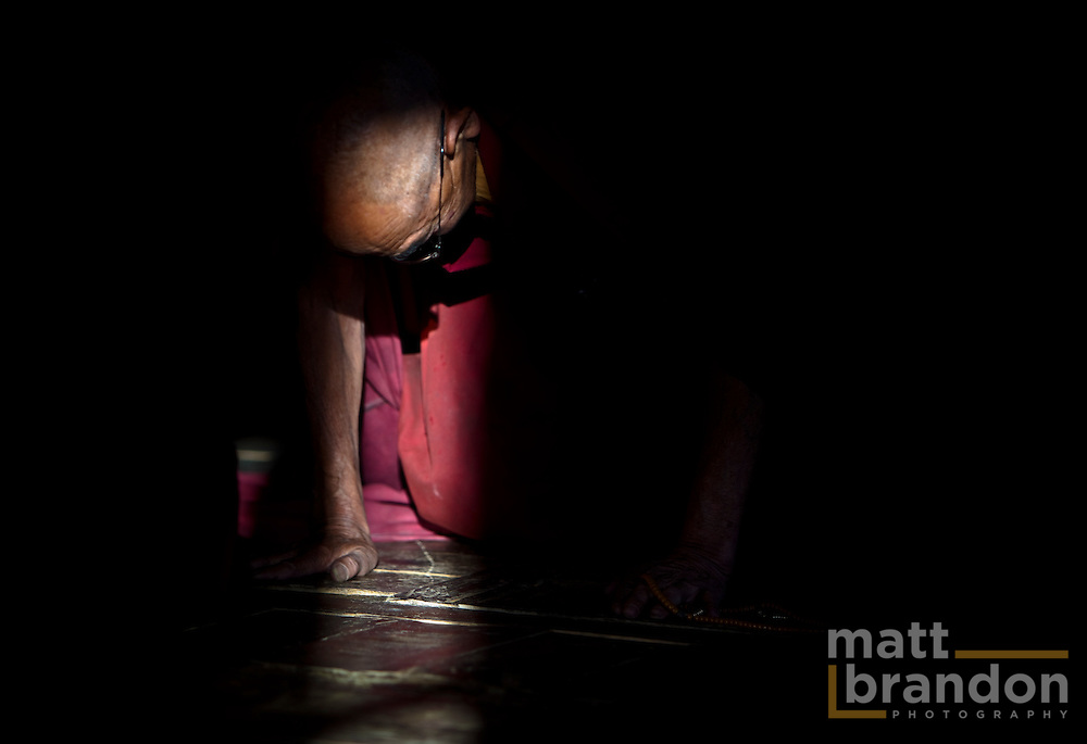 A Buddhist monk in Ladakh bows for prayer in a beam of light.