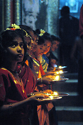 India, Gokarna, 2006. Keralan Hindu girls light the way for a special yearly ceremony in Gokarna.