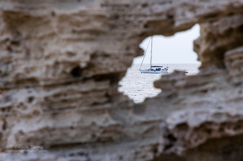 A sail boat passes through a widow created by a whole in a rock in Ibiza, Spain.