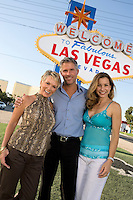 Two women and man in front of Welcome to Las Vegas sign, portrait