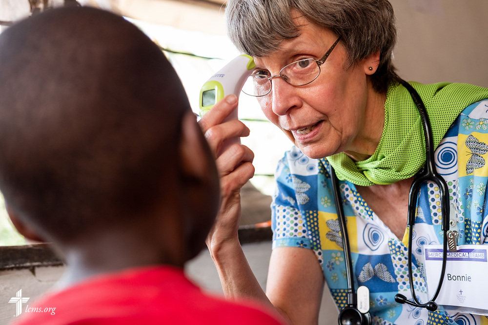 Bonnie Hartman, a member of Faith Lutheran Church, Godfrey, Ill., helps calm the anxiety of a young patient as she demonstrates the thermometer on the fourth day of the LCMS Mercy Medical Team on Thursday, May 10, 2018, in the Yardu village outside Koidu, Sierra Leone, West Africa. LCMS Communications/Erik M. Lunsford